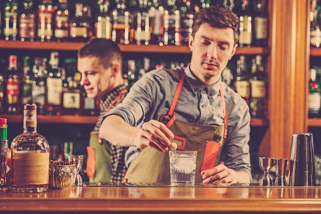 Barman especialista está fazendo um cocktail na boate.