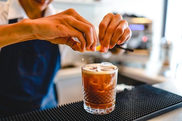 Barman especialista está preparando uma bebida alcoólica em um clube noturno. barman profissional prepara coquetel