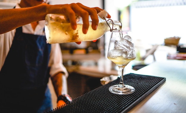 Barman especialista está preparando uma bebida alcoólica em uma boate. barman profissional prepara coquetel