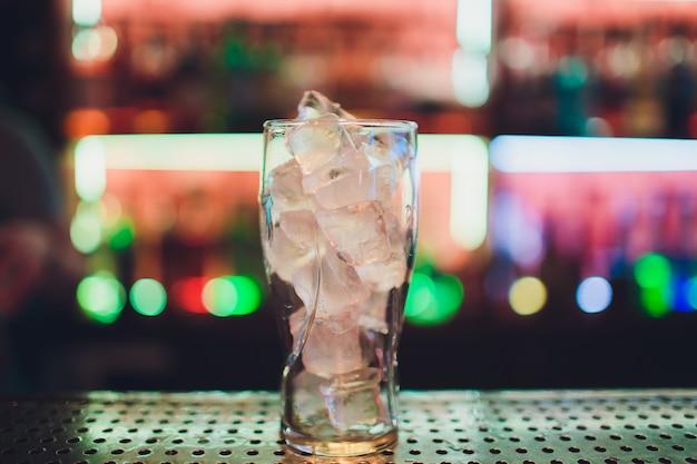 Barman espremendo suco de limão fresco em um copo usando espremedor de citrinos e espirrando para fora fazendo um coquetel alcoólico.