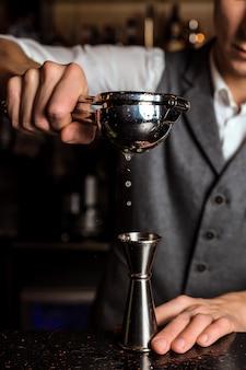 Barman espremendo suco para uma coqueteleira
