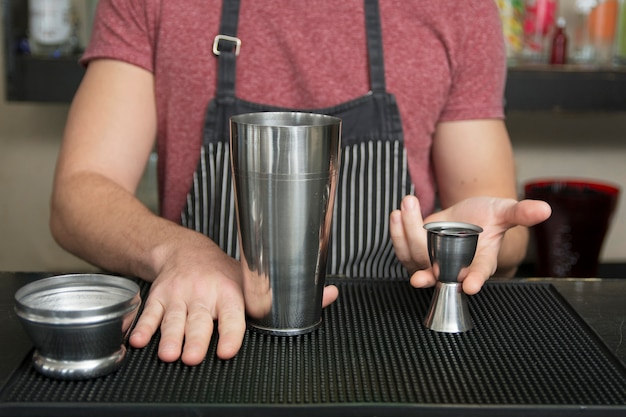 Barman está adicionando ingrediente no shaker no balcão de bar