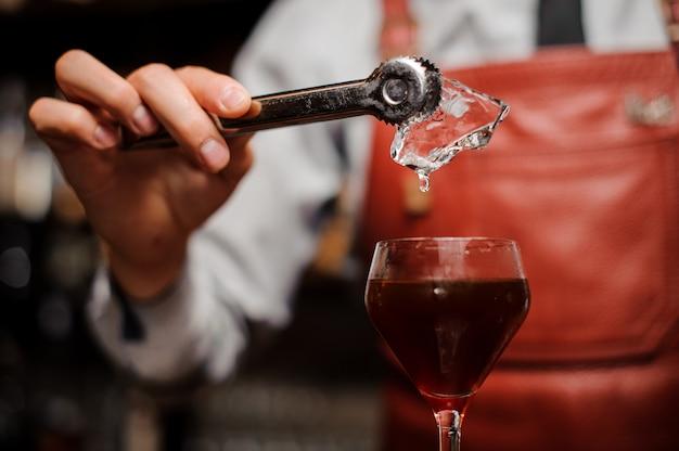 Barman está colocando um gelo no coquetel