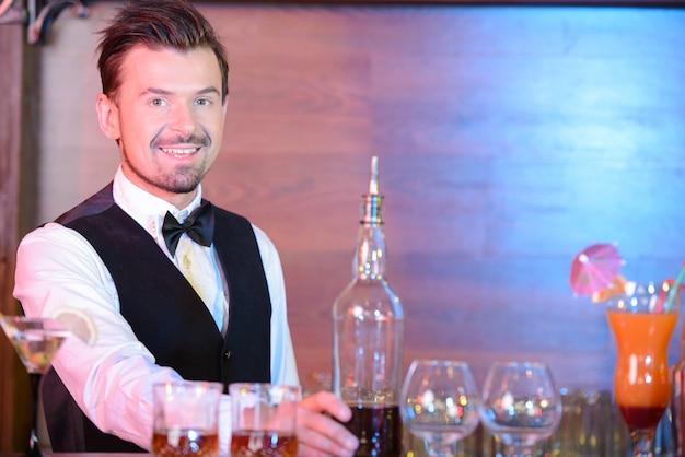 Barman está fazendo cocktail no balcão do bar.
