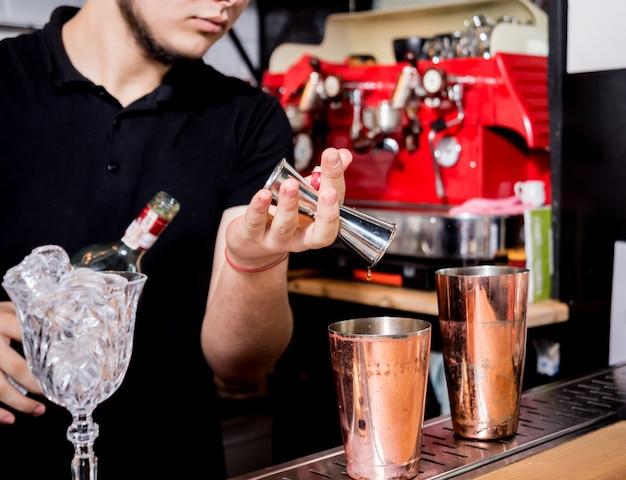 Barman está fazendo um coquetel no balcão do bar. coquetéis frescos. barman no trabalho. restaurante. vida noturna.