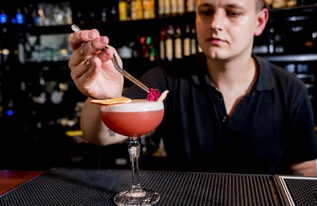 Barman está fazendo um coquetel no balcão do bar. coquetéis frescos. barman no trabalho.
