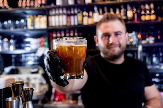 Barman está fazendo um coquetel no balcão do bar. coquetéis frescos.