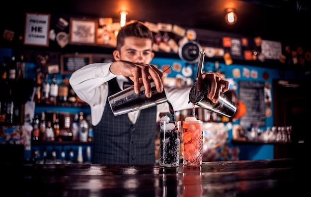 Barman experiente prepara um coquetel em pé perto do balcão do bar