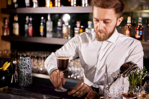 Barman fazendo bebida alcoólica e café. derramando bebida