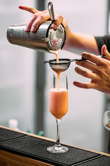 Barman fazendo um coquetel doce com shaker e copo na mesa