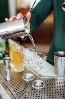 Barman fazendo um coquetel no bar: derramando uma bebida de uma coqueteleira em um copo