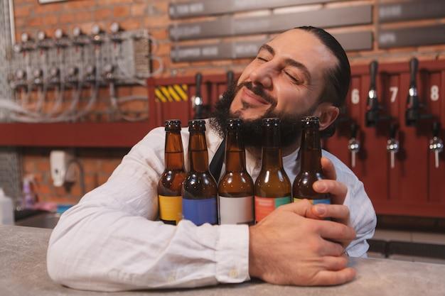 Barman feliz sorrindo com os olhos fechados e abraçando garrafas de cerveja