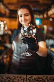 Barman feminina de avental segurando um copo