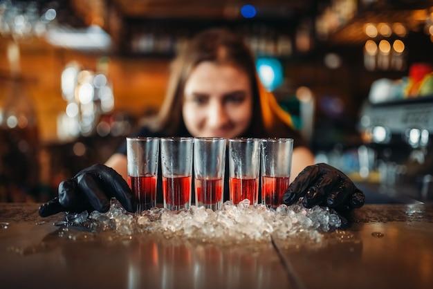 Barman feminino de luvas colocando bebidas no gelo