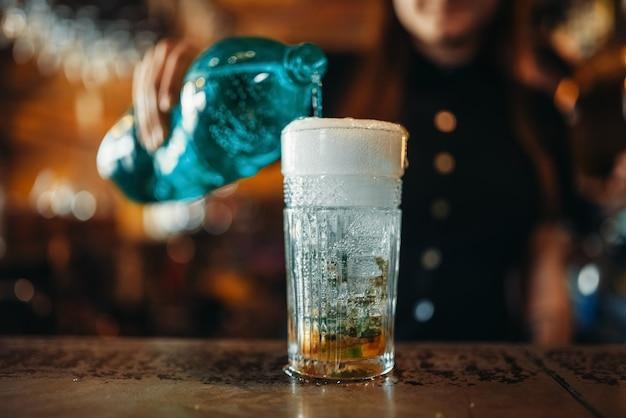 Barman feminino derrama água gaseificada em um copo