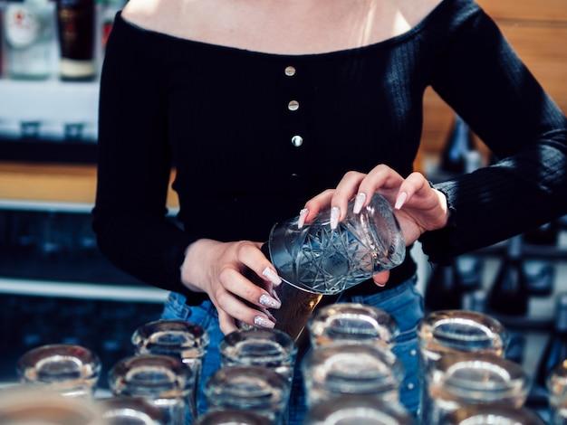 Barman feminino derramando bebida de vidro