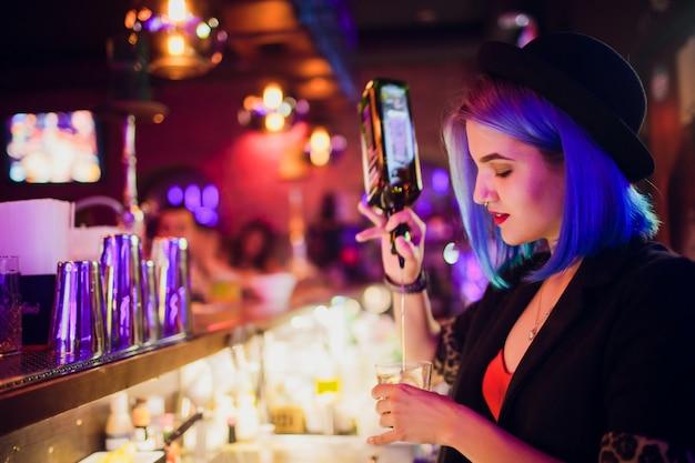 Barman feminino fazendo cocktail usando shaker in pub.
