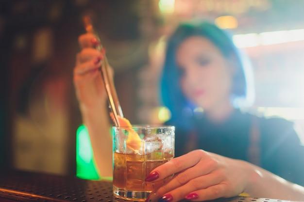 Barman feminino pulverizando o fresco delicioso coquetel para servi-lo no balcão da barra de aço.