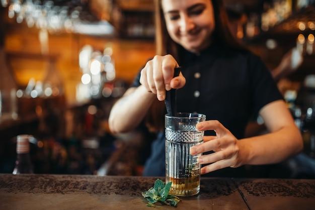 Barman feminino se misturando no balcão do bar