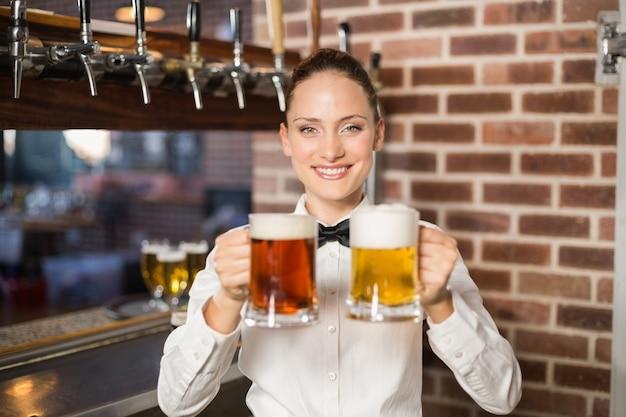 Barman feminino segurando cervejas