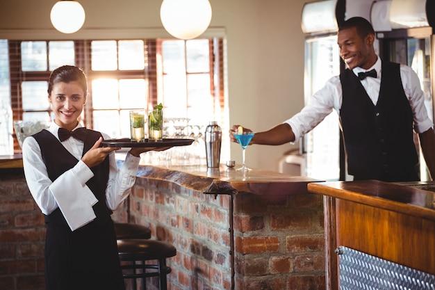 Barman feminino segurando uma bandeja com dois copo de cocktail