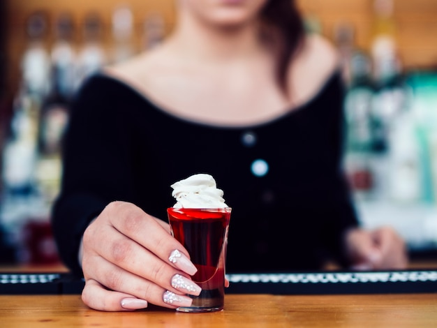 Barman feminino, servindo tiro colorido vermelho