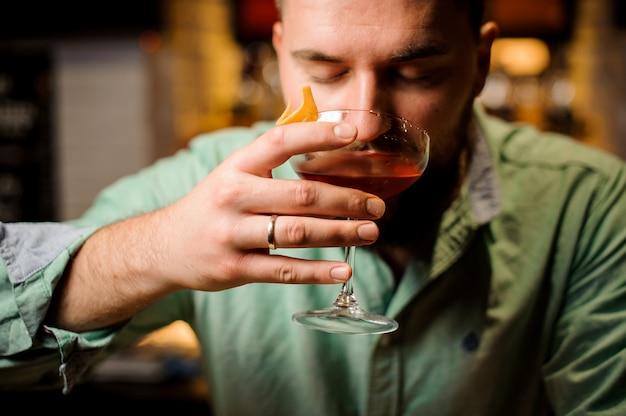Barman holdind cocktail com os olhos fechados