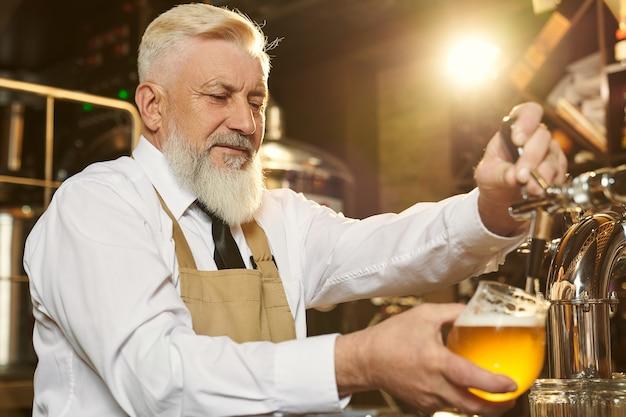 Barman idoso, alegre, servindo cerveja light em um copo com torneira de cerveja. especialista barbudo em avental marrom olhando para vidro. conceito de fabricação de cerveja e comércio.