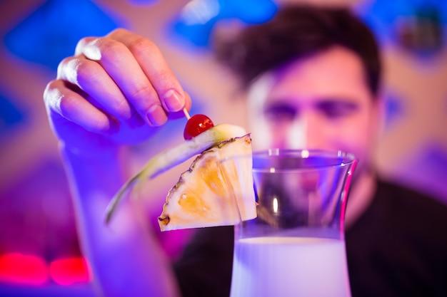 Barman, mantendo frutas no copo de coquetel