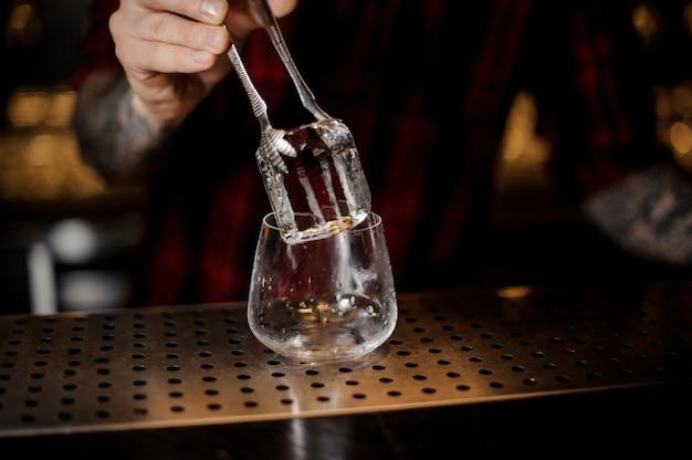 Barman mão colocando um grande cubo de gelo em um uísque dof