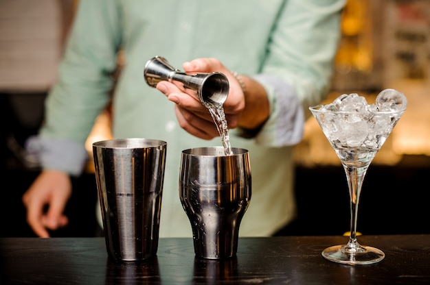 Barman mãos derramando bebida em uma coqueteleira para preparar um cocktail close-up