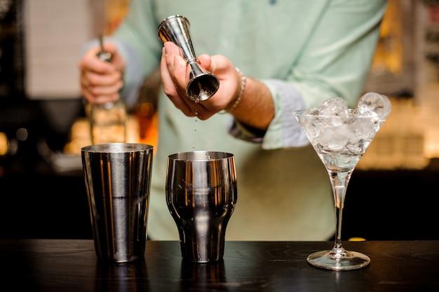 Barman mãos derramando bebida em uma coqueteleira para preparar um cocktail