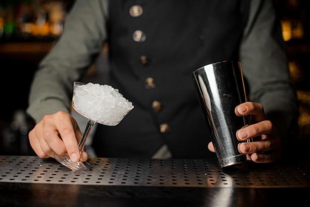 Barman mãos segurando uma coqueteleira e um copo de coquetel