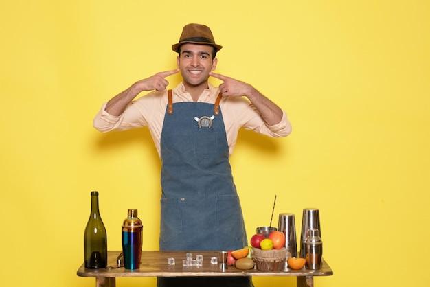 Barman masculino de frente para a mesa com bebidas e coquetéis na parede amarela bar de bebidas alcoólicas à noite