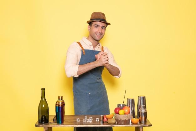 Barman masculino de frente para a mesa com bebidas e coquetéis na parede amarela bebida masculina do bar de bebidas alcoólicas à noite