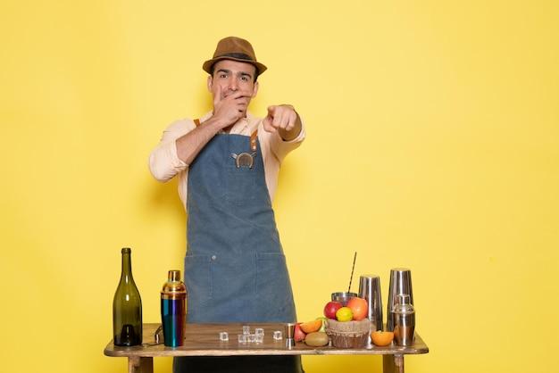 Barman masculino de frente para a mesa com bebidas e coquetéis rindo na parede amarela bar do clube de bebidas alcoólicas à noite