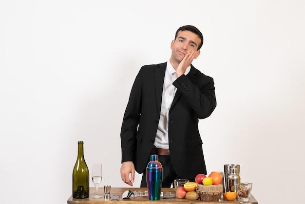 Barman masculino de frente para a mesa com bebidas, posando na mesa branca, à noite, bar de bebidas masculinas do clube de bebidas alcoólicas