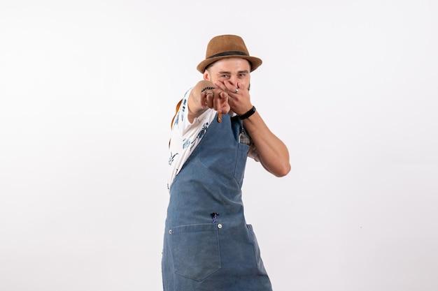 Barman masculino de vista frontal posando e apontando com uma expressão engraçada no clube de trabalho de bar de bebidas alcoólicas à noite na parede branca