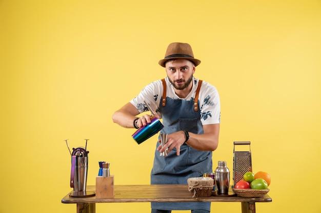 Barman masculino de vista frontal preparando uma bebida dentro de uma coqueteleira na parede amarela bar noturno com álcool bebida cor de trabalho