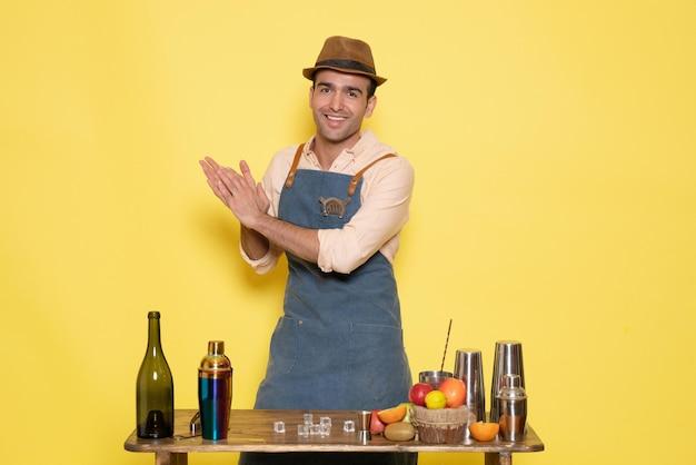 Barman masculino em frente à mesa com bebidas e coquetéis batendo palmas na parede amarela bar de bebidas alcoólicas masculinas à noite