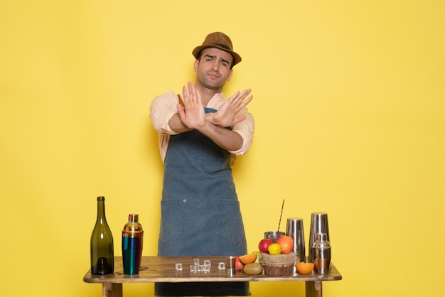 Barman masculino em frente à mesa com bebidas e coquetéis na mesa amarela, bebida à noite, bar de bebidas alcoólicas clube de cores