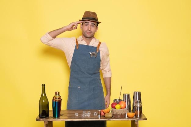 Barman masculino em frente à mesa com bebidas e coquetéis na parede amarela, bebida à noite, bar de bebidas alcoólicas clube de cores