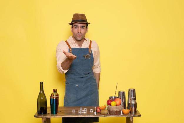 Barman masculino em frente à mesa com bebidas e coquetéis na parede amarela