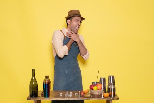 Barman masculino em frente à mesa com bebidas e shakers se chocando na parede amarela bar de bebidas alcoólicas à noite