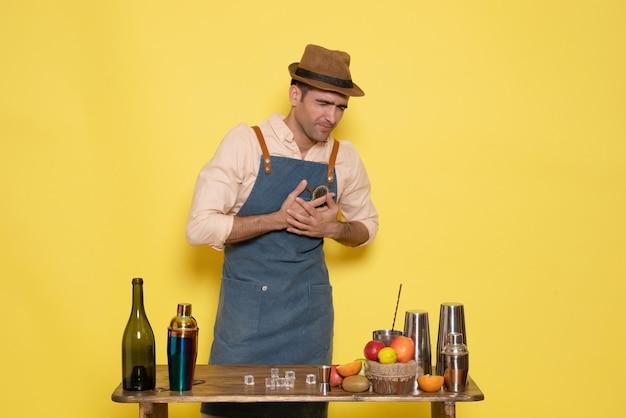Barman masculino em frente à mesa com bebidas e shakers tendo problemas com o coração na parede amarela.