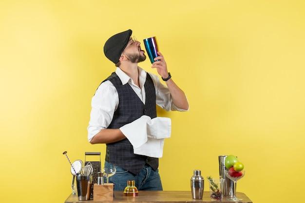 Barman masculino em frente à mesa, com coquetéis, coqueteleira com toalha na parede amarela, bebida alcoólica para jovens de boate