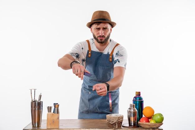 Barman masculino em frente à mesa com coquetéis e frutas na parede branca bar de bebidas alcoólicas serviço de bebidas à noite