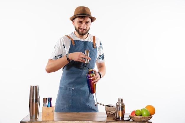 Barman masculino em frente à mesa do bar preparando uma bebida na coqueteleira na mesa branca.