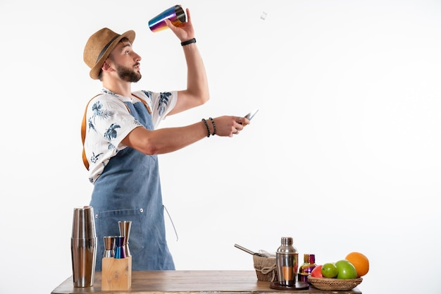 Barman masculino em frente à mesa do bar preparando uma bebida na coqueteleira na parede branca.