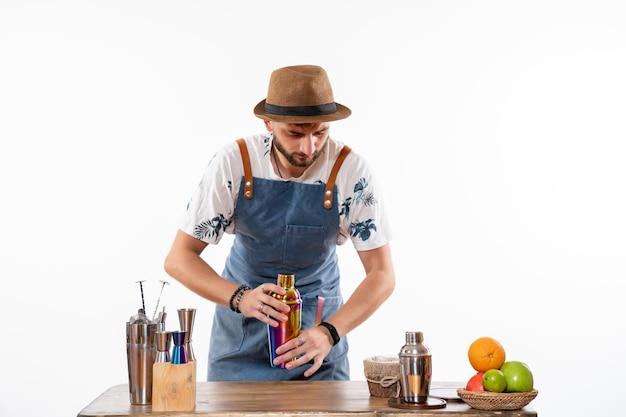 Barman masculino em frente à mesa do bar preparando uma bebida na coqueteleira no piso branco
